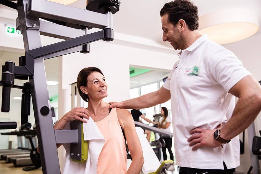 Trainer mit Trainierende am Gerät