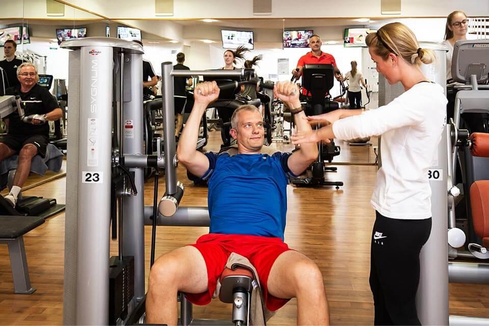 Trainierender am Gerät mit Trainerin